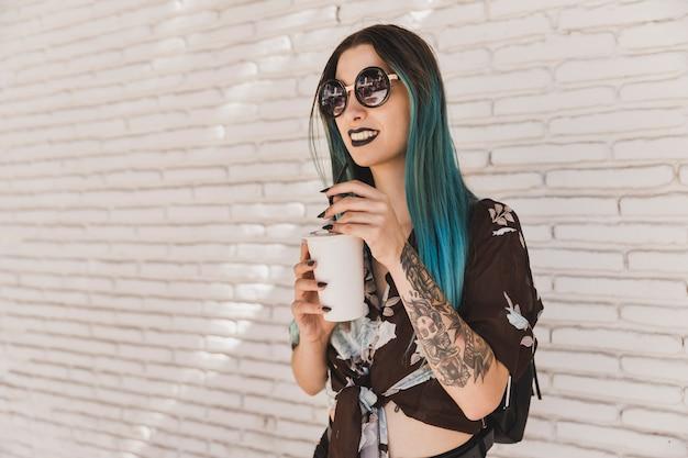 Moderna mulher jovem e bonita usando óculos escuros, segurando o copo de café descartável Foto gratuita