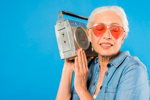 Moderna mulher sênior com rádio vintage Foto gratuita