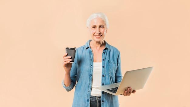 Moderno, mulher sênior, com, laptop, e, café Foto gratuita