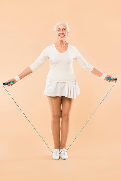 Moderno, mulher sênior, com, pular corda Foto gratuita