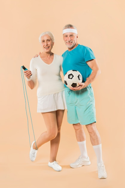 Moderno, par velho, com, pular corda, e, futebol Foto gratuita