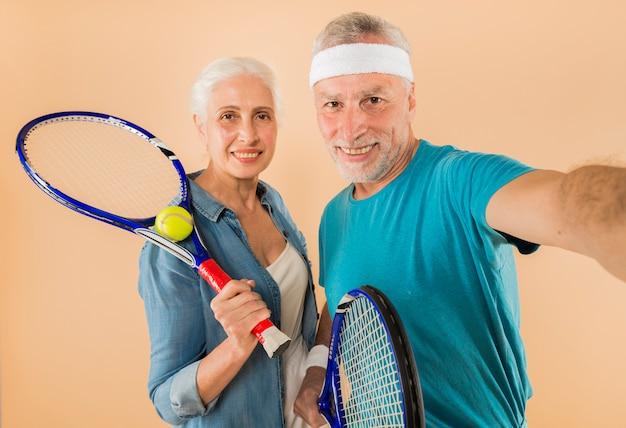 Moderno, par velho, com, raquete tênis, tendo, selfie Foto gratuita