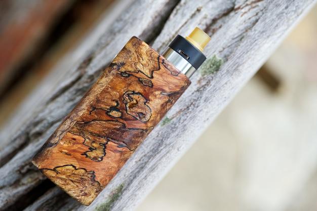 Mods de caixa de madeira estabilizada natural de ponta com atomizador de gotejamento rebuildable, dispositivo vaping, foco seletivo Foto Premium