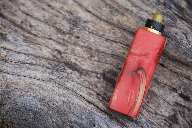 Mods de caixa regulada de madeira estabilizada natural vermelha de alta qualidade com atomizador de gotejamento rebuildable na textura de madeira de madeira natural, equipamento de vaporizador, foco seletivo Foto Premium