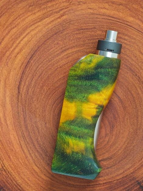 Mods de caixa regulamentada de madeira estabilizada verde amarelo de burl poplar com atomizador de gotejamento rebuildable em fundo de textura de madeira natural Foto Premium