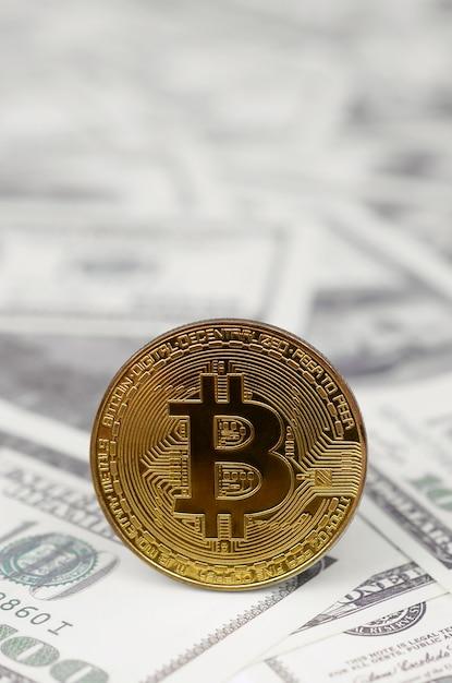 Moeda de bitcoin de ouro sobre fundo de notas de dólar Foto Premium