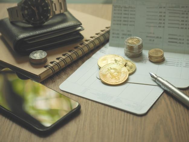 Moeda de bitcoin e caderneta e caneta e smartphone na tabela de uso para o conceito de negócio Foto Premium
