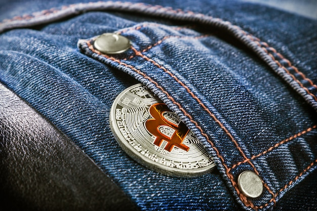 Moeda de criptomoeda bitcoin no bolso da calça jeans Foto Premium