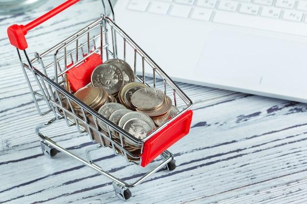 Moeda de dinheiro no mini carrinho de compras ou carrinho Foto Premium