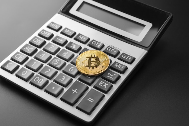 Moeda de ouro bitcoin na calculadora Foto Premium