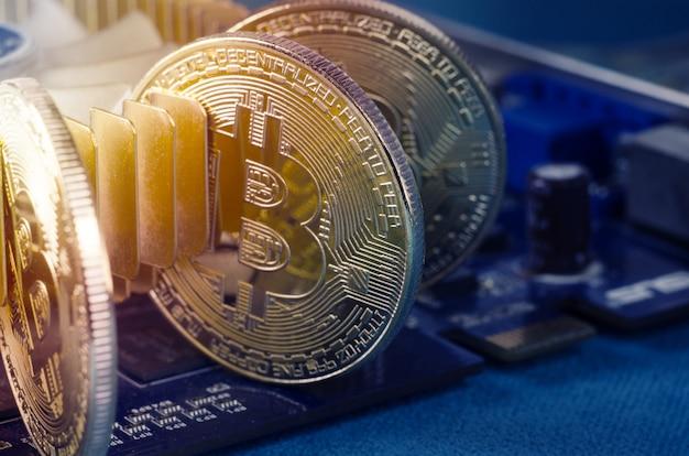 Moeda física de bitcoin do ouro em uma placa de vídeo do computador. nova criptografia mundial independente. Foto Premium