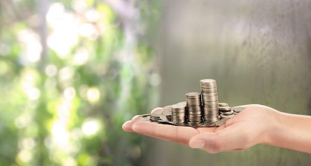 Moedas colocadas em cima. enquanto a mão de um homem derramando moedas Foto Premium