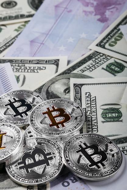 Moedas de bitcoin no fundo das notas de dólares Foto Premium