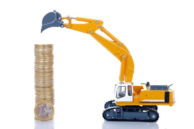 Moedas de dinheiro de euro com escavadeira isolada no espaço em branco Foto gratuita