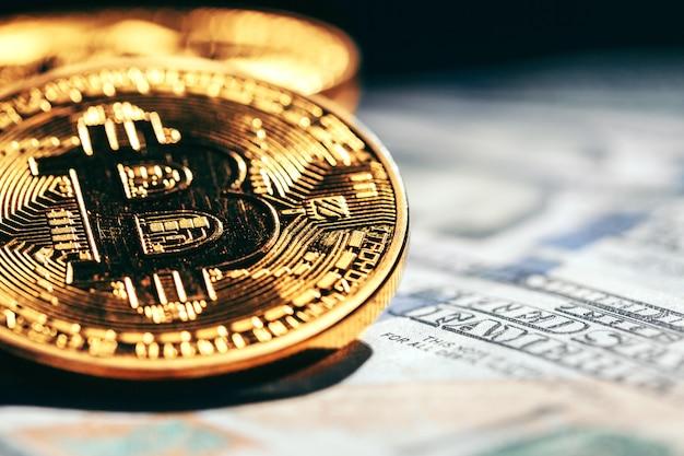 Moedas de ouro bitcoin em um papel dólares dinheiro Foto Premium