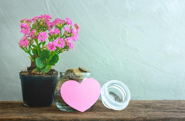 Moedas de ouro em um frasco de vidro com nota de papel de coração na mesa de madeira Foto Premium