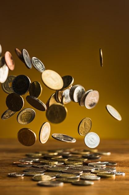 Moedas de prata e ouro e moedas caindo na mesa de madeira Foto gratuita