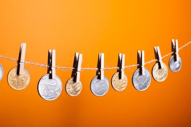 Moedas de rublo russo pendurado em prendedores de roupa de madeira em um fundo laranja Foto Premium