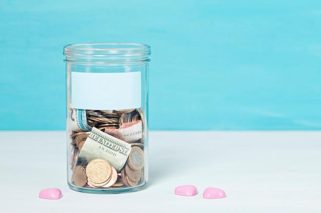Moedas e notas em pote de dinheiro de vidro, doações financeiras, conceito de caridade Foto Premium