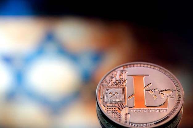 Moedas litecoin, contra a bandeira israelense, conceito de dinheiro virtual, close-up. imagem conceitual Foto Premium