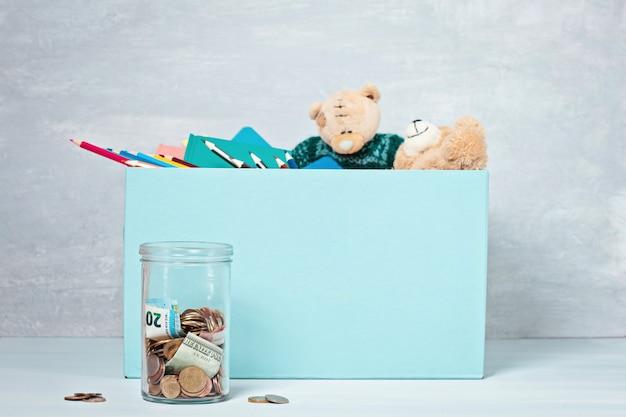 Moedas, notas em pote de dinheiro e caixa com doações Foto Premium