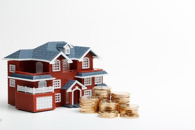 Moedas rmb empilhadas em frente ao modelo habitacional (preços das casas, compra de casas, imóveis, conceito de hipoteca) Foto gratuita