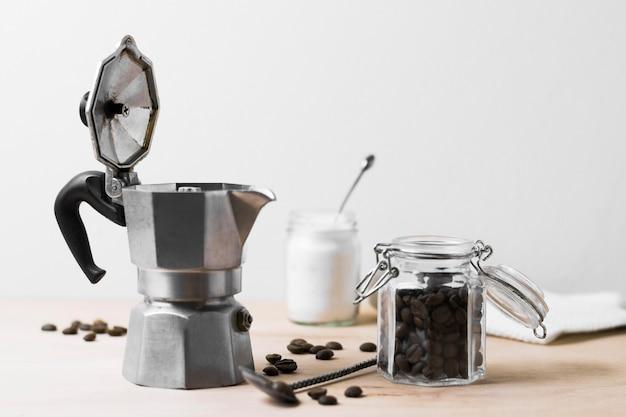 Moedor de café e grãos de café vista frontal Foto gratuita