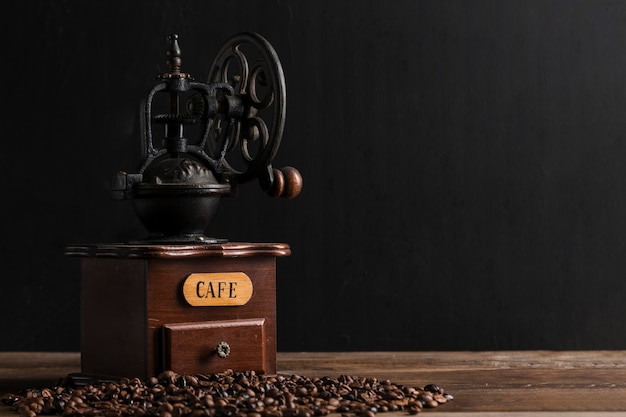 Moedor de café vintage perto de grãos dispersos Foto gratuita