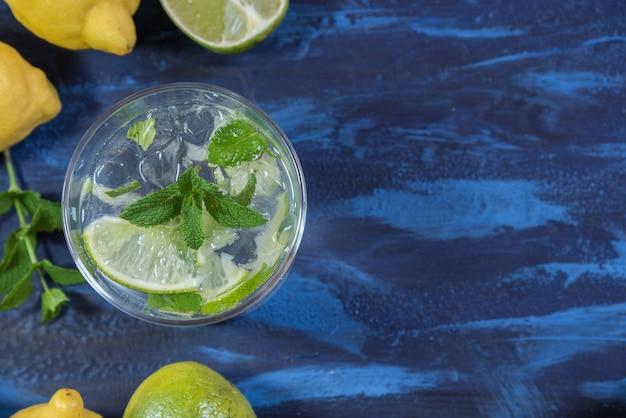 Mojito cocktail com seus ingredientes em uma mesa azul Foto Premium