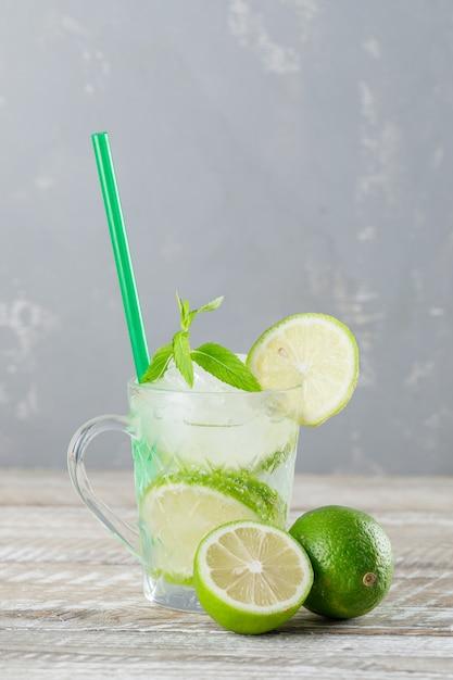 Mojito gelado cocktail em um copo com limão, palha, vista lateral de hortelã no fundo de madeira e gesso Foto gratuita