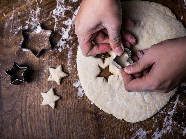 Molde do corte do uso da mão do cozinheiro chefe de pastelaria para cortar a massa da cookie na mesa de cozinha. Foto Premium