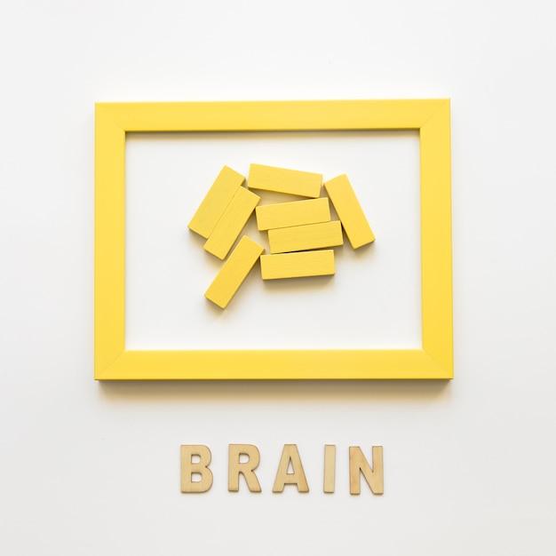 Moldura amarela com blocos de madeira perto da palavra cérebro Foto gratuita