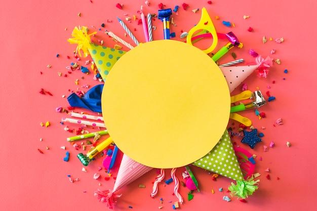 Moldura amarela em branco sobre acessórios de festa em fundo vermelho Foto gratuita