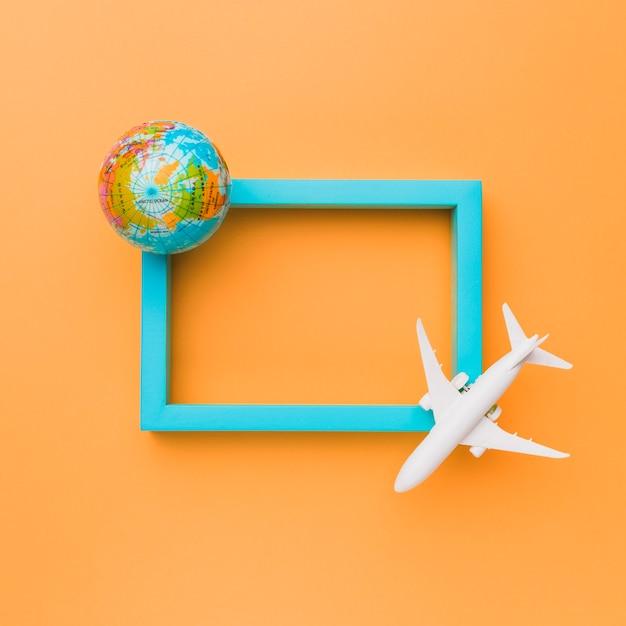 Moldura azul com avião e globo Foto gratuita