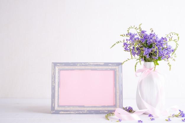 Moldura branca com linda flor roxa em vaso na mesa de madeira branca Foto Premium