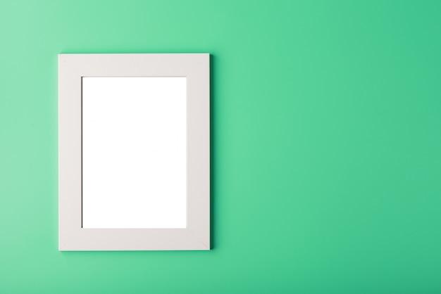 Moldura branca com um espaço vazio em um fundo verde. Foto Premium