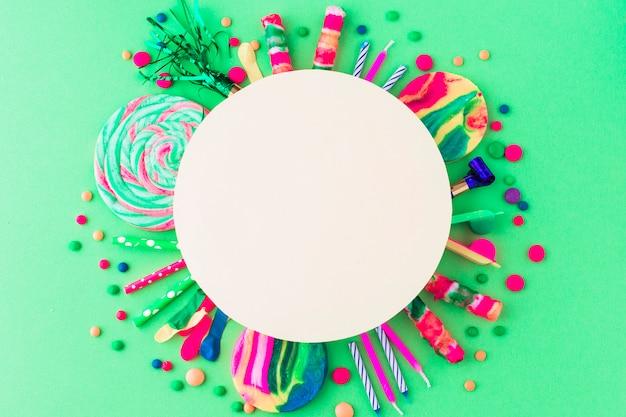 Moldura branca em branco sobre acessórios de festa e doces em fundo verde Foto gratuita