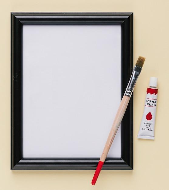 Moldura branca vazia com tubo de tinta e pincel Foto gratuita