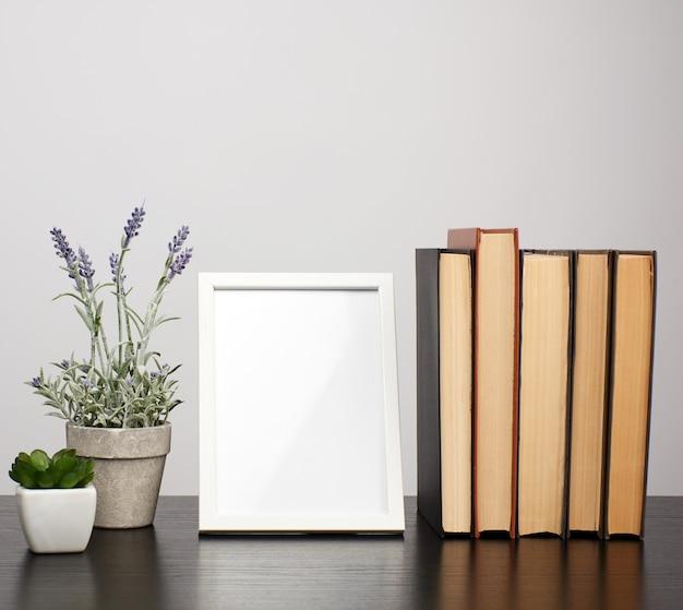 Moldura branca vazia, pilha de livros e um pote de lavanda crescente Foto Premium