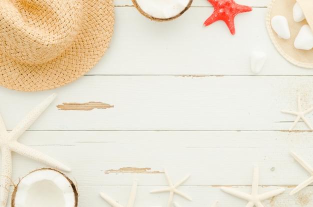 Moldura de chapéu de palha, estrelas do mar e cocos Foto gratuita