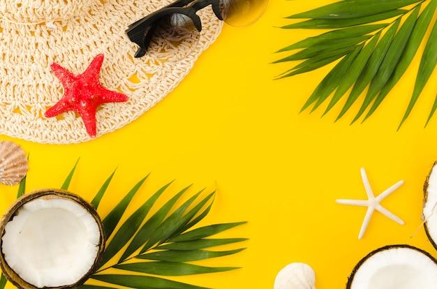Moldura de chapéu de palha, folhas de palmeira e cocos Foto gratuita