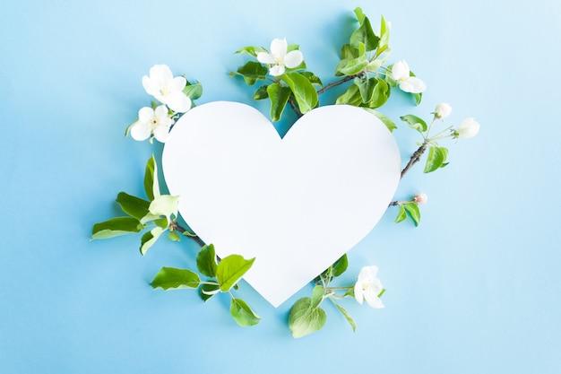 Moldura de coração com maçã flor em fundo azul Foto Premium
