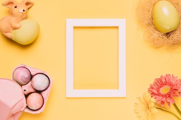 Moldura de madeira branca em branco com ovos de páscoa; estatueta de coelho e gerbera flor em fundo amarelo Foto gratuita