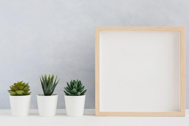Moldura de madeira em branco com três tipo de planta de cacto em vaso na mesa Foto gratuita
