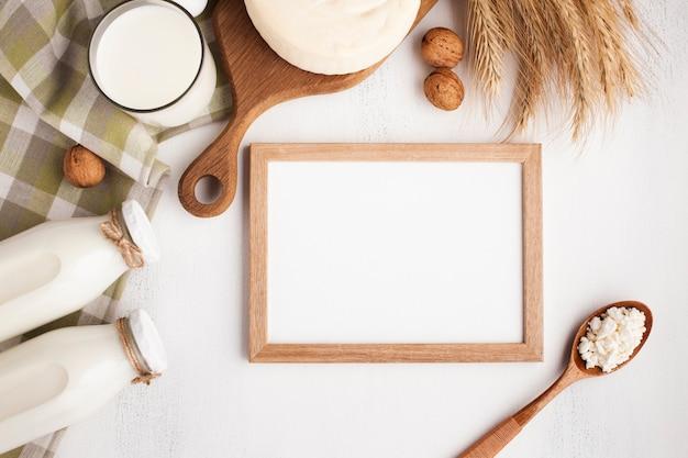 Moldura de madeira mock-up com produtos lácteos Foto gratuita