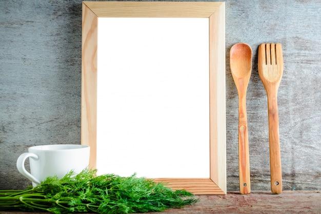 Moldura de madeira vazia com fundo branco isolado e utensílios de cozinha e endro verde Foto Premium