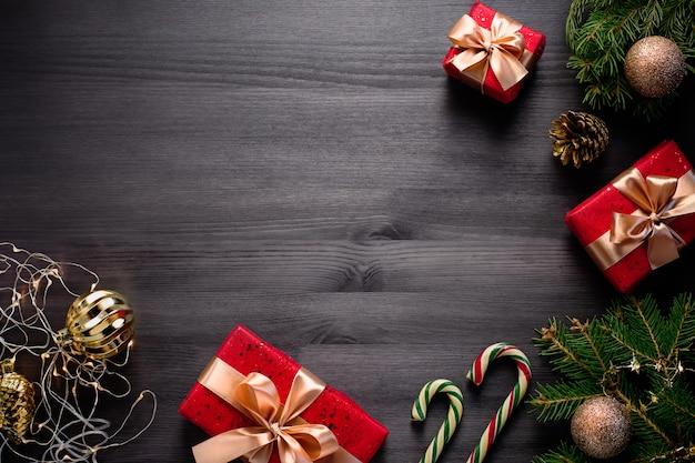 Moldura de natal com pinheiros, presentes, enfeites dourados em madeira escura Foto Premium
