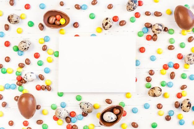 Moldura de páscoa com ovos de chocolate, doces coloridos Foto Premium