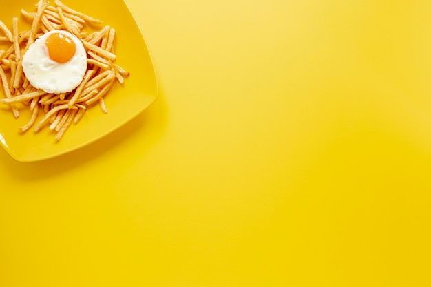 Moldura de vista superior com ovo e batatas fritas no prato Foto gratuita