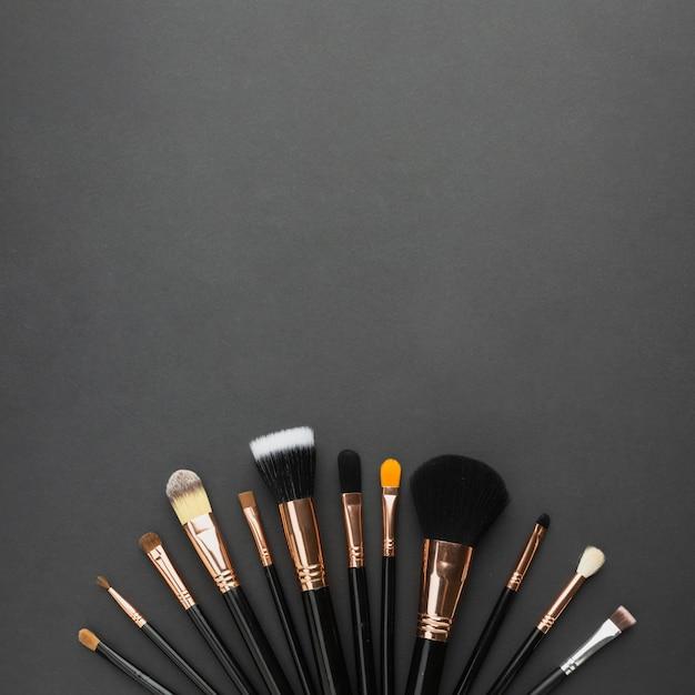 Moldura de vista superior com pincéis de maquiagem e fundo preto Foto gratuita